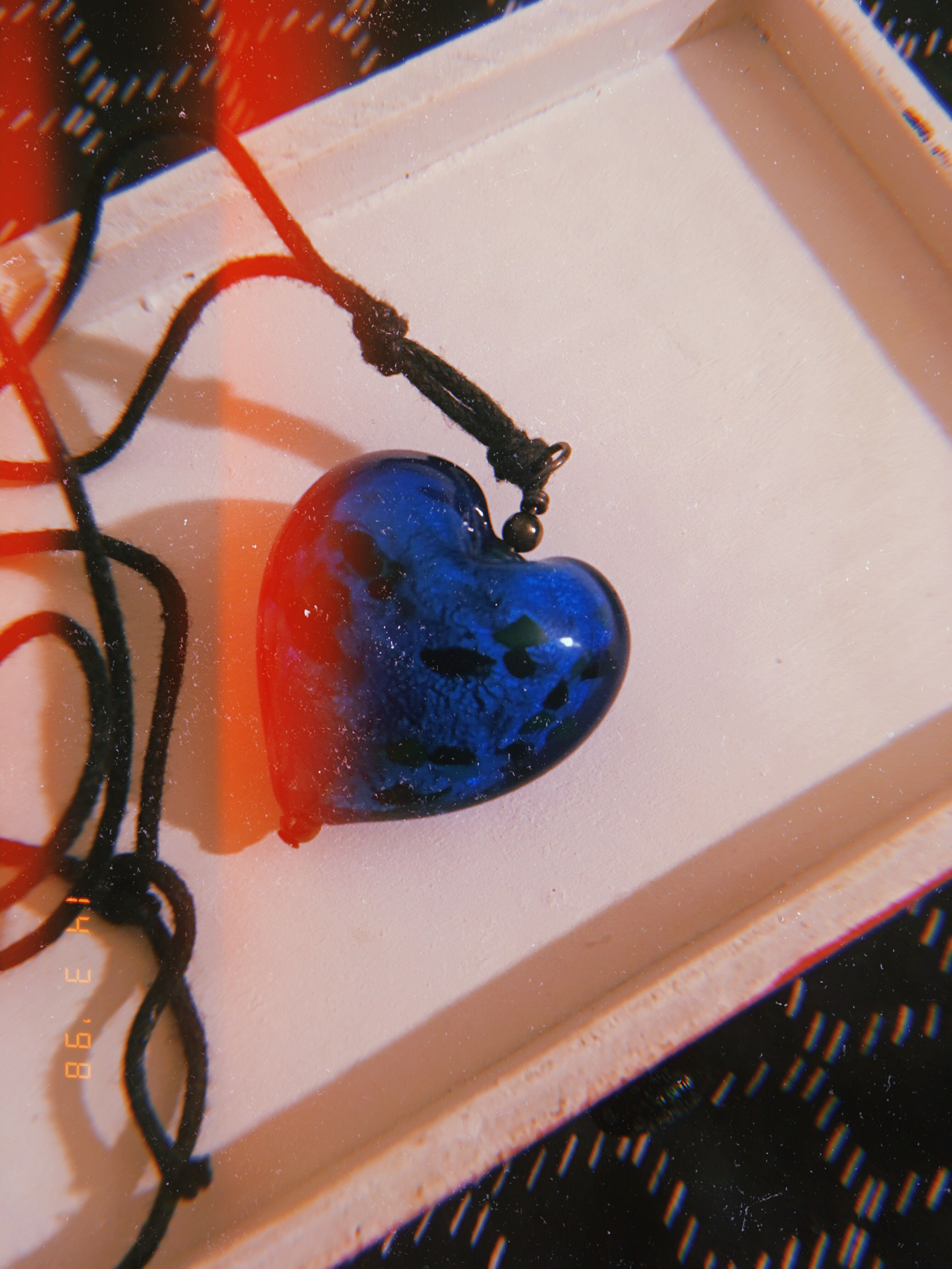 blue glass heart pendant on black cord necklace