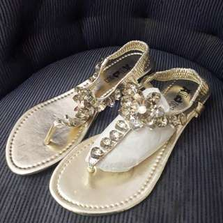 Gold sandals with fake crystals.