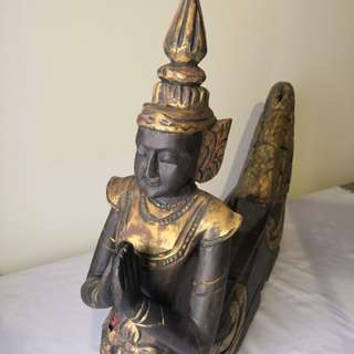 Antique wood carving of figurine in boat shape
