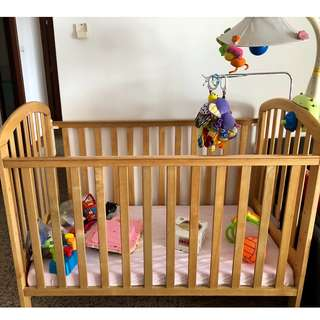 Sturdy wooden baby cot with mattress and bedding