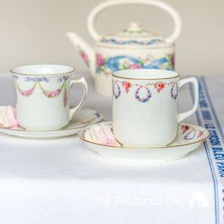 Two pretty antique English bone china demitasse cups and saucers, ribbon bows, swags and garlands