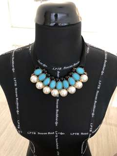 Blue and white pearl necklace with black ribbon