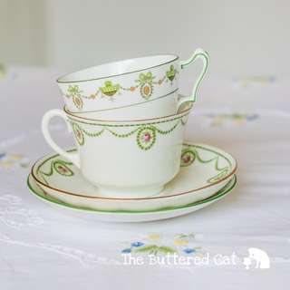 Two lovely antique English bone china teacups and saucers, ribbon bows, cameos, swags and garlands