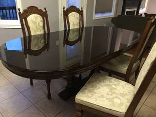 Oval  dining room table with glass top and four chairs