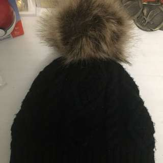 Black winter hat with fur ball