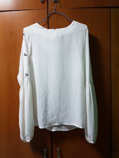 White top with embellishments on the sleeves