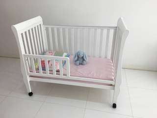 Beautiful white baby cot with teething rails and IKEA spring mattress