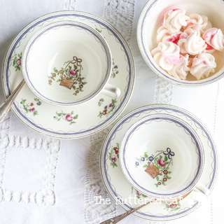 A pair of antique hand-decorated English teacups, basket of flowers, ribbon bow, ' His and Hers ' teacups