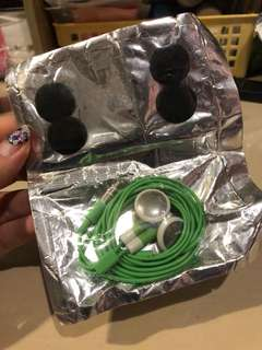 Green earpiece earphones in packaging