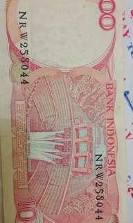 Uang SERATUS RUPIAH jadul dan antik langkah dengan nimer seri NRW258041 tahun pembuatan 1984 bergambar BURUNG Goura victoria dan bendungan Tangga Asahan.