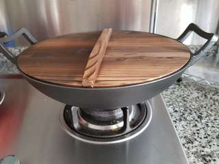 Cast iron wok with wooden cover