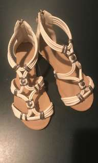 Cream sandals with silver detailing and a zippered back