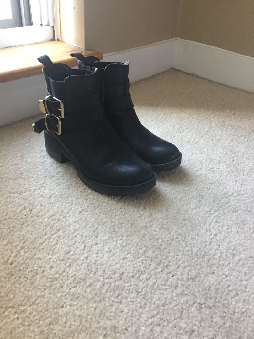 Black Chelsea boots with gold buckles