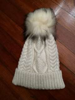 White Winter hat with big fluffy fur ball