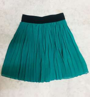 Pleated green skirt — above the knee length