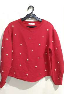 Red pullover with pearl details.