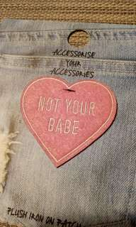 "Iron on patch in pink heart and ""not your babe"" words"