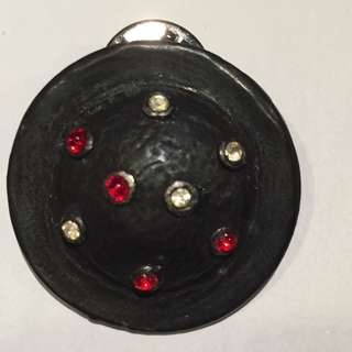 Round black ceramic or resin lapel pin with red and white crystals