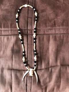 Ivory bead necklace with pair of tusks for prayer