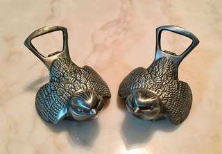 A pair of metal bird figurines bottle opener