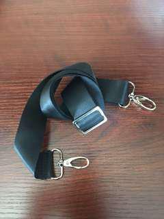 Black shoulder strap with gold buckles