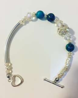 Silver and a hint of blue stone beads, and  Swarovski crystal bracelet with charm.