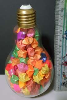 A bottle of hand made stars in lightbulb glass container