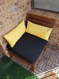 Solid acacia wood outdoor sofa with black seat cushion.