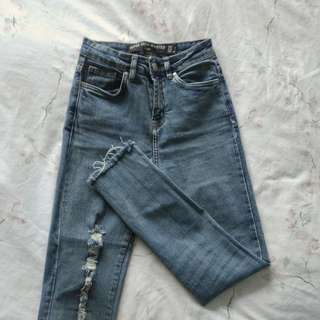 Faded blue distressed denim jeans
