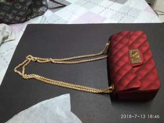 Jelly sling bag with chain sling channel motif in red color