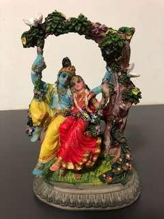 Lord Krishna sitting on a swing with Radha