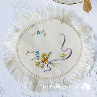 Very pretty antique fringed doily, hand-embroidered floral bouquet in blue and yellow, tied with lilac / purple ribbon