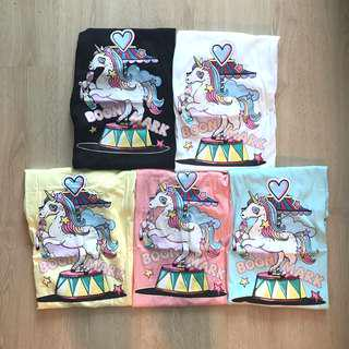 Flying Unicorn on a carousel in pastel shades graphic T Shirts top