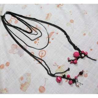 Long layered necklace with black chain and pink charms