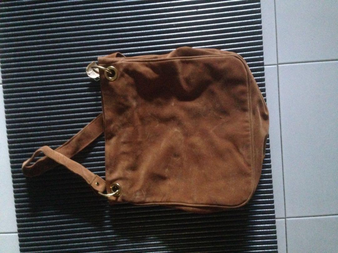 New, unused ladies sling bag, color golden brown.