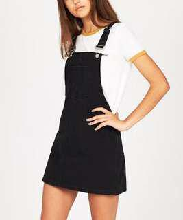Subtitled black pinafore dress
