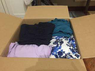A box full of dresses and skirts with some bonus belts and clutch