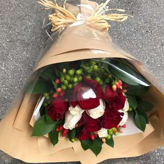 Cream and red roses with red and green berries bouquet