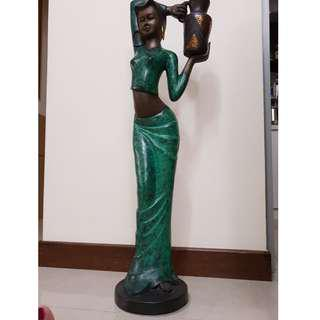 Tall metal lady with jug sculpture