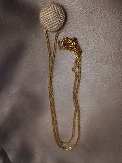 Gold colored necklace and pendant