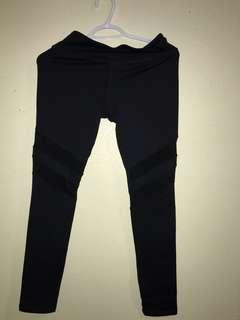 Black leggings with mesh detailing at the knee