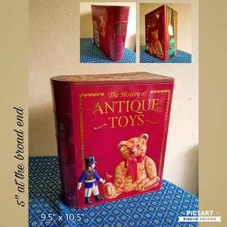 "Collectable Old Biscuits Tin in the shape of an Antique Book title ""The History of Antique Toys"". It has motif of old toy bear and tin soldier. Great as Film-prop or Display. Size as in photos. Good Condition, clean inside. $5 offer! whatsapp 96337309."