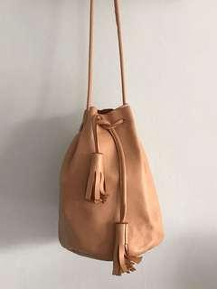 Tan leather drawstring bucket bag with tassels