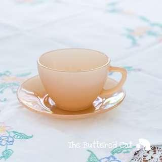 Vintage peach-coloured glass cup and saucer