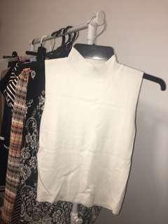White sleeveless turtle neck knit top