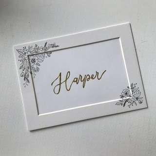 Custom card in gold foil calligraphy with flower drawing in frame