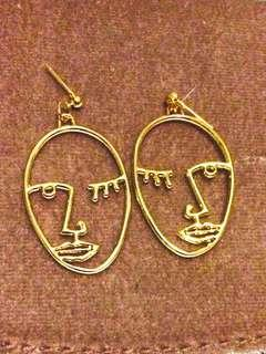 Gold wire face earrings
