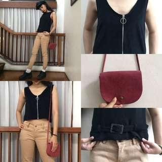 Chino pants, buckled top, zipper top, and a red sling bag