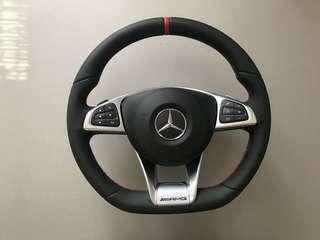 AMG steering wheel with red stitching, sports ring and paddle shift.
