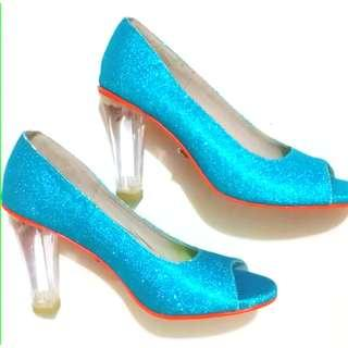 Blue glitter peep toe shoes with orange outer soles and transparent heels